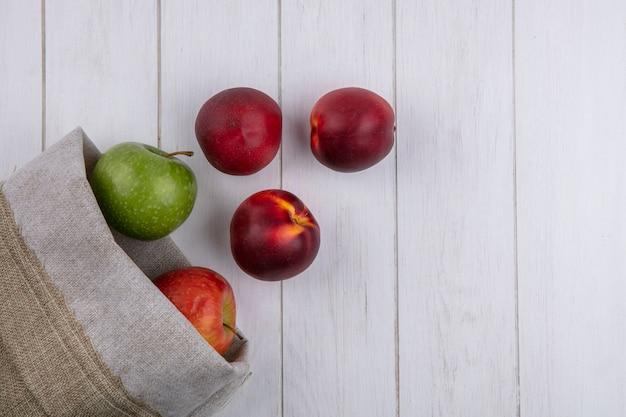 Bovenaanzicht van perziken met appels in een jutezak op een wit oppervlak