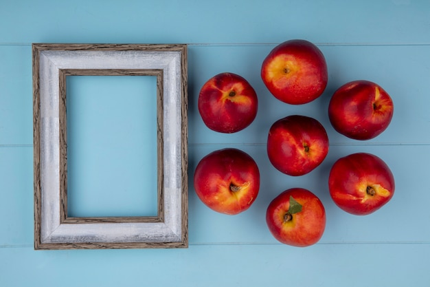 Bovenaanzicht van perziken met grijs frame op een lichtblauw oppervlak