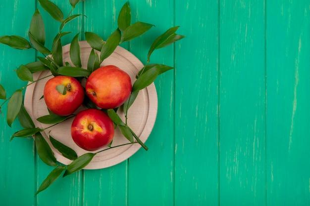 Bovenaanzicht van perziken op een houten dienblad met een geruite handdoek op een groen oppervlak