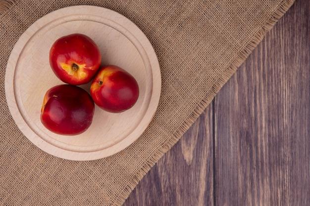 Bovenaanzicht van perziken op een houten dienblad op een beige servet op een houten oppervlak