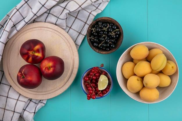 Bovenaanzicht van perziken op een stand met rode en zwarte bessen en met abrikozen op een blauwe ondergrond