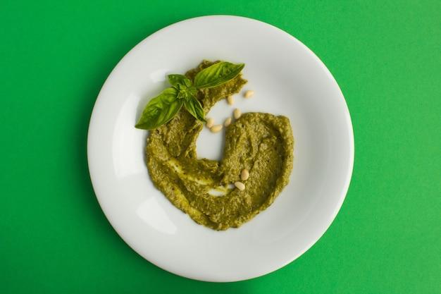 Bovenaanzicht van pesto saus op de witte plaat op het groene oppervlak