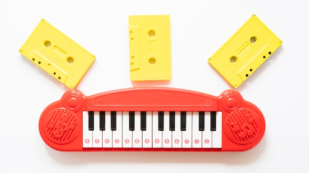 Bovenaanzicht van piano speelgoed en cessettes op effen achtergrond