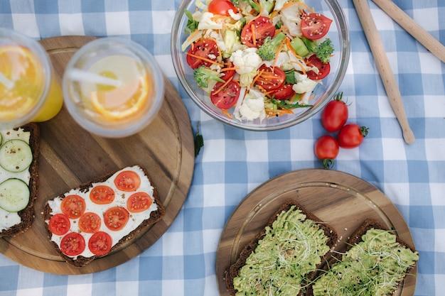 Bovenaanzicht van picknickmand met gezonde veganistische sandwiches op blauw geruite deken in park