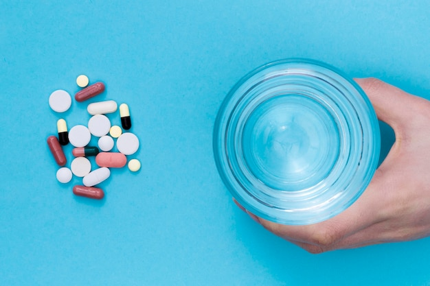 Bovenaanzicht van pillen met hand met glas water