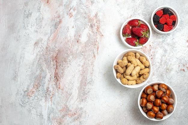 Bovenaanzicht van pinda's en hazelnoten met verse aardbeien op witte ondergrond