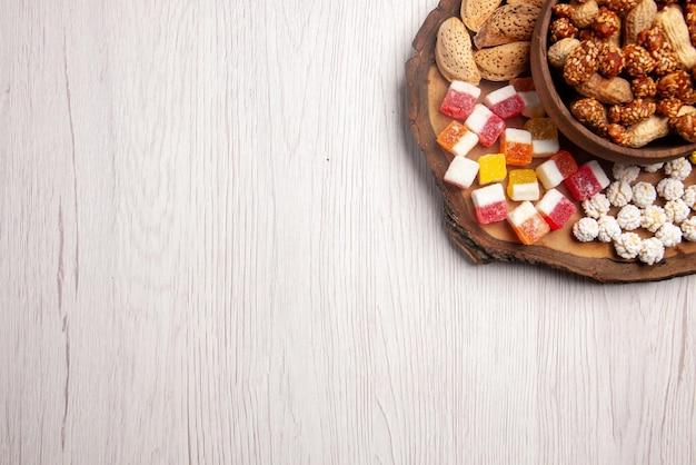 Bovenaanzicht van pinda's houten snijplank met snoep en kom met pinda's aan de linkerkant van de witte tafel