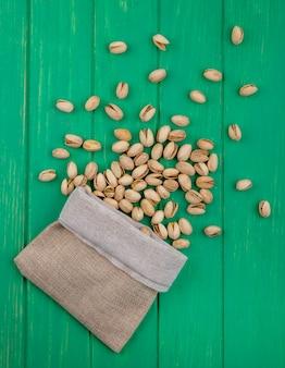 Bovenaanzicht van pistachenoten in een jutezak op een groen oppervlak