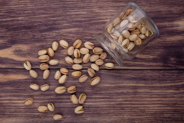 Bovenaanzicht van pistachenoten in een pot op een houten oppervlak