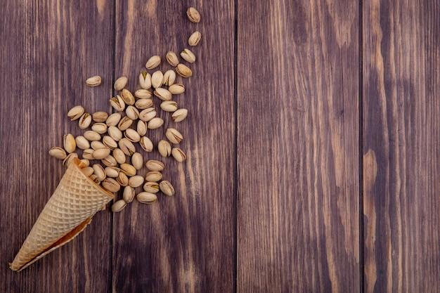 Bovenaanzicht van pistachenoten in een wafelkegel op een houten oppervlak