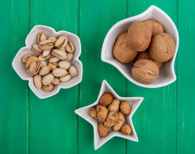 Bovenaanzicht van pistachenoten met hazelnoten en walnoten in kommen op een groen oppervlak