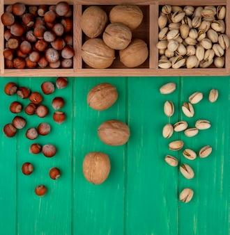 Bovenaanzicht van pistachenoten met hazelnoten en walnoten op een houten standaard op een groen oppervlak