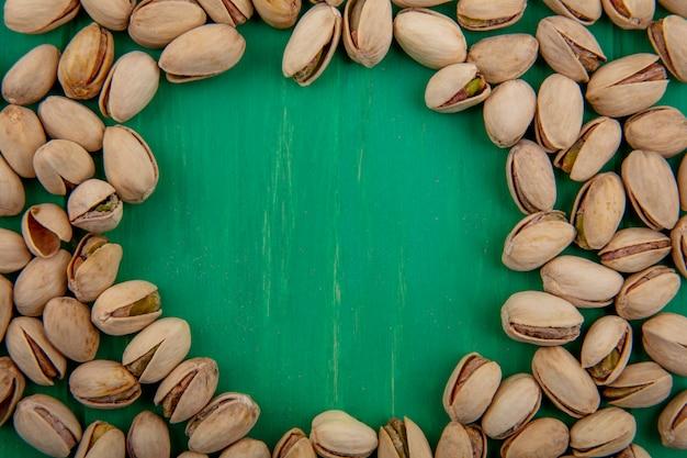 Bovenaanzicht van pistachenoten op een groen oppervlak