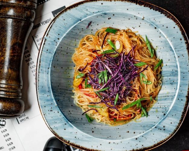 Bovenaanzicht van pittige aziatische noedels met groenten en rode kool in een kom