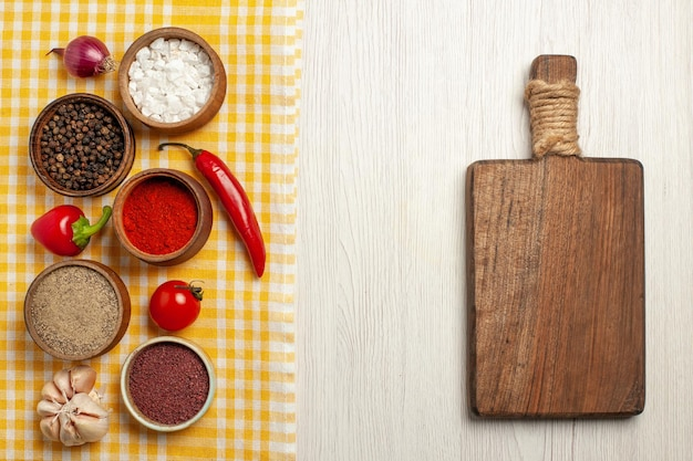 Bovenaanzicht van pittige kruiden met groenten op wit