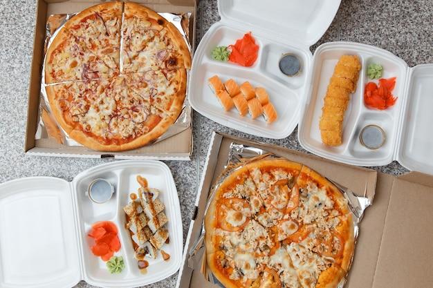 Bovenaanzicht van pizza en sushi. levering in containers en dozen.