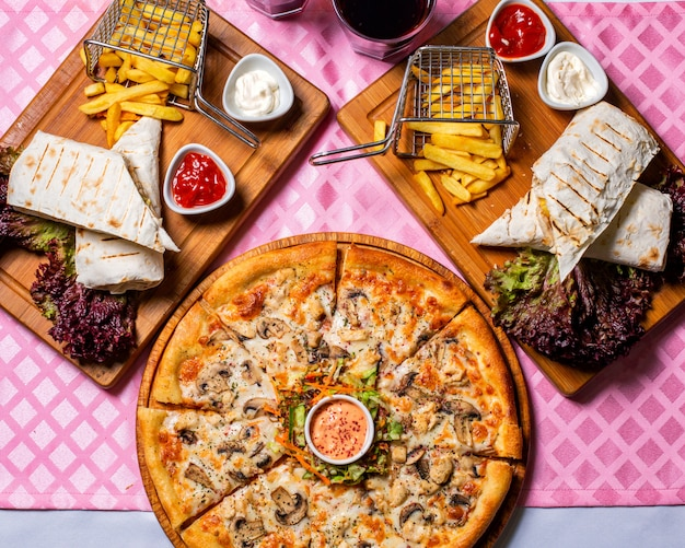 Bovenaanzicht van pizza met kip en champignons geserveerd met saus en groenten salade op een houten plaat