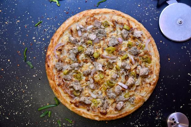 Bovenaanzicht van pizza met krokante korst van ui, kip