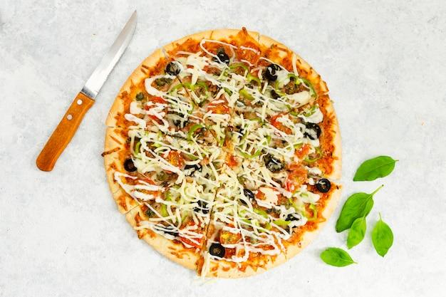 Bovenaanzicht van pizza met mes en mint