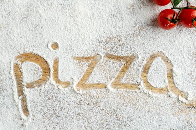 Bovenaanzicht van pizza woord geschreven in bloem