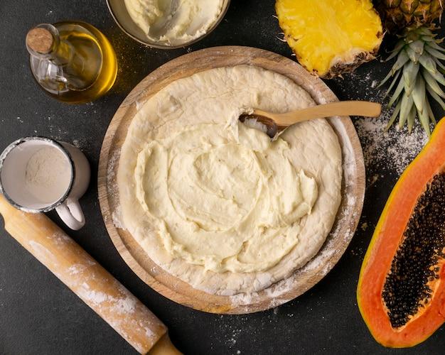 Bovenaanzicht van pizzadeeg in kom met ananas en papaja