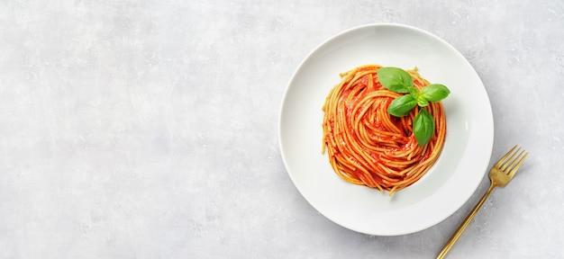 Bovenaanzicht van plaat eith pasta in tomatensaus en basilicum