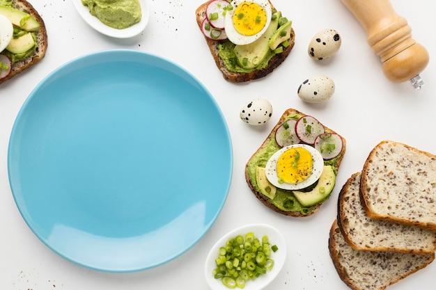 Bovenaanzicht van plaat met broodjes ei en avocado