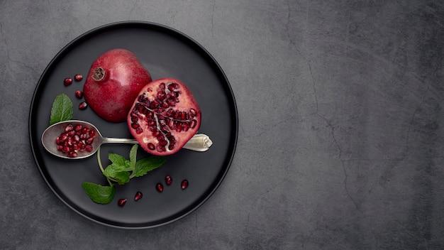 Bovenaanzicht van plaat met munt en granaatappel