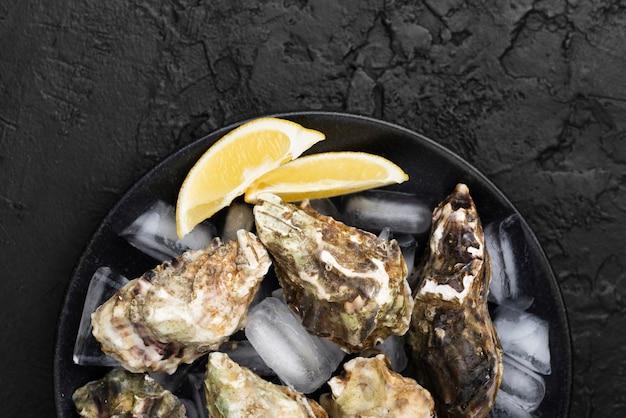 Bovenaanzicht van plaat met oesters en plakjes citroen