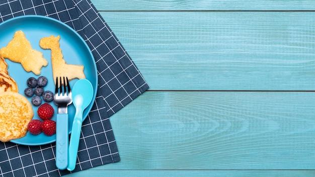 Bovenaanzicht van plaat met pannenkoeken voor babyvoeding en kopie ruimte