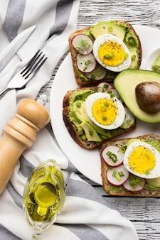 Bovenaanzicht van plaat met sandwiches met ei en avocado en bestek