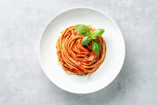Bovenaanzicht van plaat met spaghetti in tomatensaus en basilicum