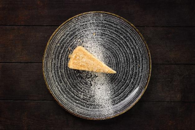 Bovenaanzicht van plaat met stuk kokos cake op houten achtergrond