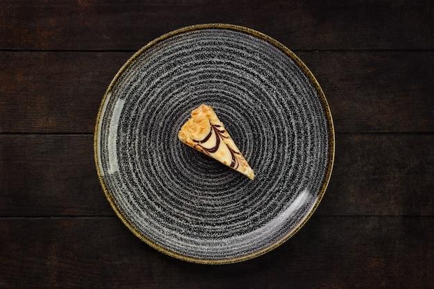Bovenaanzicht van plaat met stuk pindakaas op houten achtergrond