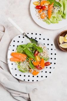 Bovenaanzicht van plaat met wortelen en andere gezonde voeding