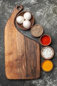 Bovenaanzicht van plaat staan met kruiden en kom met eieren aan de zijkant op donkergrijze achtergrond