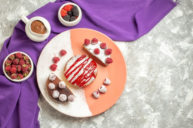 Bovenaanzicht van plaat van dessert op paars servet met bessen en chocolade aan kant op marmeren achtergrond