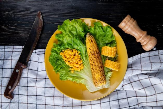 Bovenaanzicht van plaat van hele en gesneden likdoorns met maïs zaden en sla met mes op doek en zwart