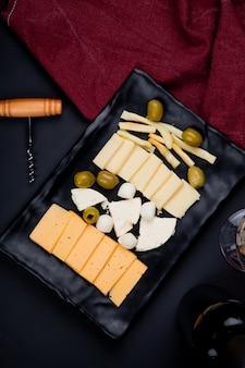 Bovenaanzicht van plaat van kaas als parmezaanse kaas en cheddar met olijven en kurkentrekker met doek op zwarte tafel