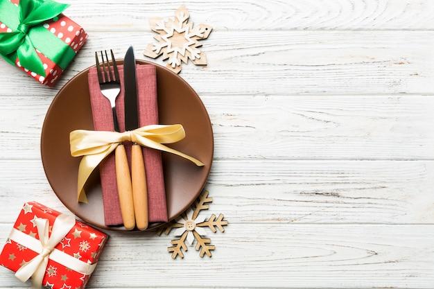 Bovenaanzicht van plaat, vork en mes geserveerd op kerst versierde houten oppervlak