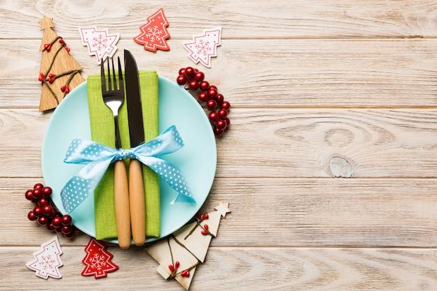 Bovenaanzicht van plaat, vork en mes geserveerd op kerstmis ingericht houten tafel. new year eve concept met kopie ruimte
