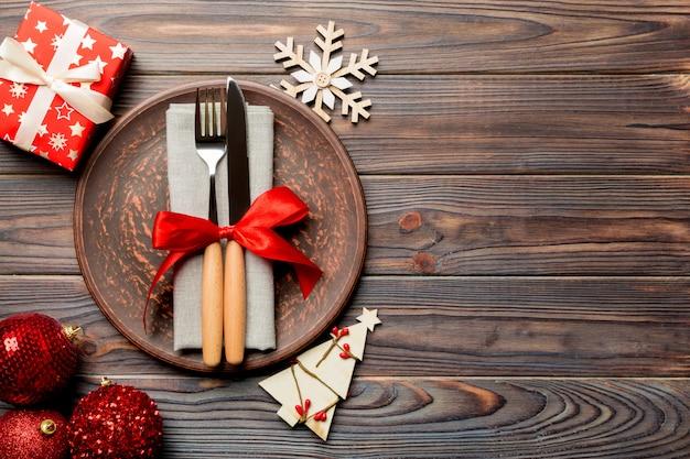 Bovenaanzicht van plaat, vork en mes geserveerd op kerstmis versierde houten oppervlak.