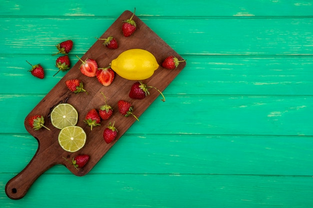 Bovenaanzicht van plakjes aardbei op een houten keukenbord op een groene houten achtergrond met kopie ruimte