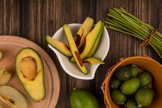 Bovenaanzicht van plakjes avocado op een kom met feijoas op een emmer op een houten muur