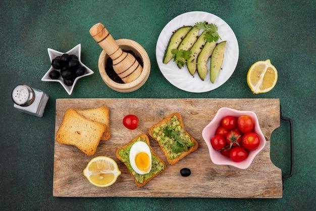 Bovenaanzicht van plakjes avocado op witte plaat met een geroosterde sneetjes brood met avocadopulp en ei op houten keukenbord met tomaten op roze kom op gre