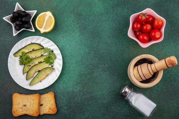 Bovenaanzicht van plakjes avocado op witte plaat met zwarte olijven lemonnd geroosterd sneetje brood aan de ene kant en tomaten op roze kom zoutvaatje aan de andere kant op gre wit