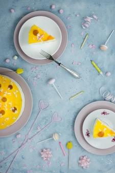 Bovenaanzicht van plakjes cake met vork en verjaardag decoraties