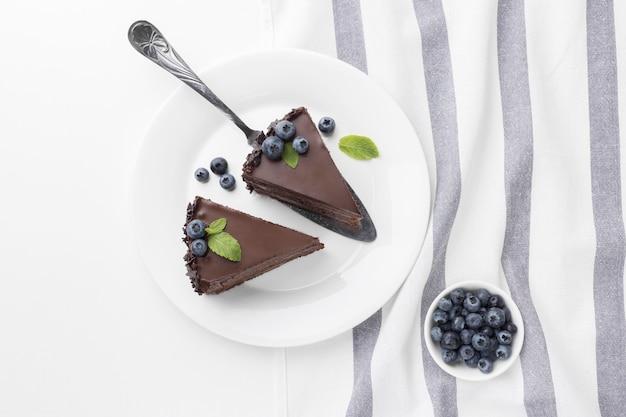 Bovenaanzicht van plakjes chocoladetaart op platen met kom met bosbessen