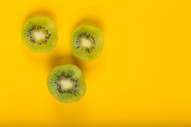 Bovenaanzicht van plakjes kiwi op een gele achtergrond. gezond eten, exotisch fruit