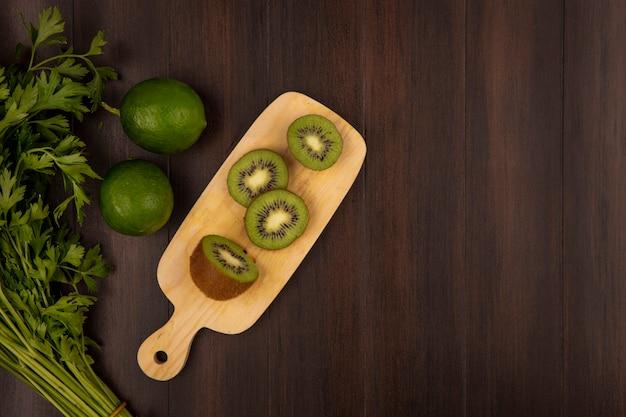 Bovenaanzicht van plakjes kiwi op een houten keukenbord met peterselie en limoenen (lemmetjes) geïsoleerd op een houten achtergrond met kopie ruimte
